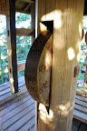 This is a Buddhist prayer wheel up in a treehouse of a structure.