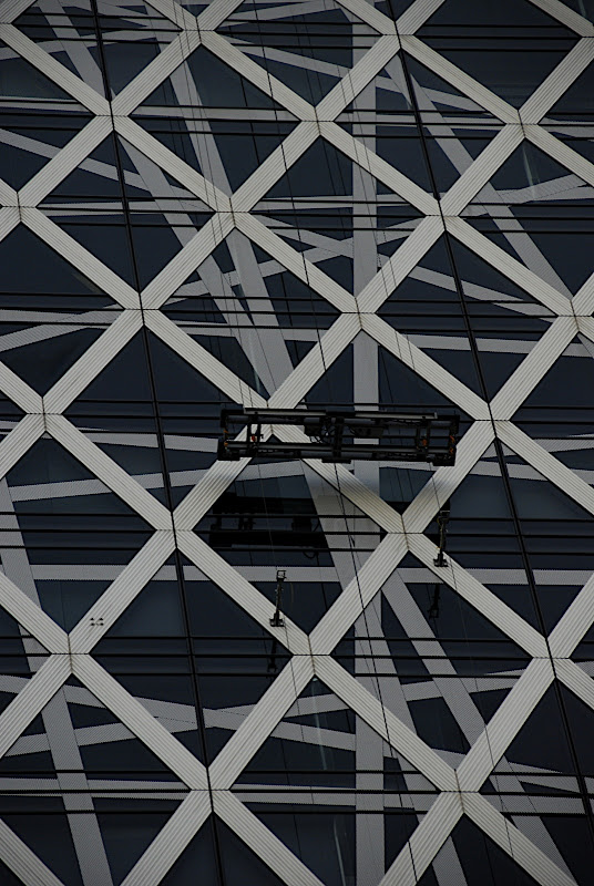 The intricate crossing structure of the fixtures holding the building's external glass coverings