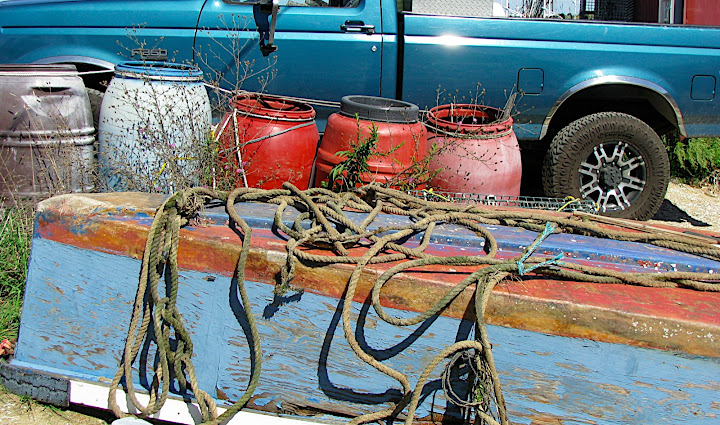 peeling rowboat hull with plastic barrels and pickup truck (study in color)