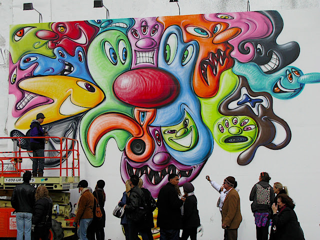 colorful cartoon characters being spray-painted on a large wall