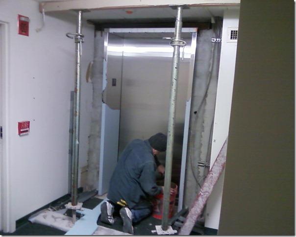 Worker installing elevator door.