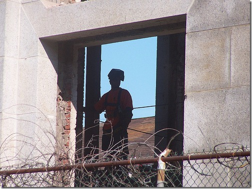 Welder in gutted building looking out at the camera from an empty window opening