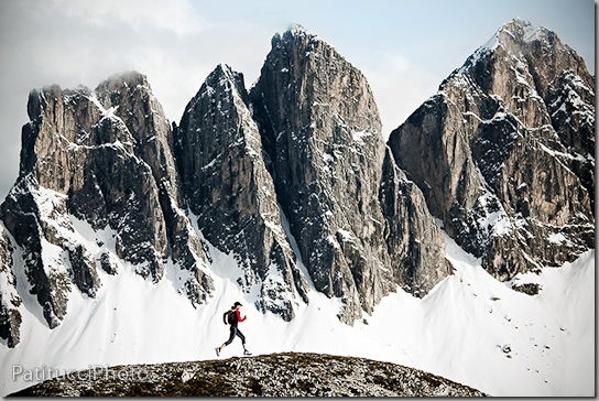 A female trail runner in the Italian Dolomites with the Geislergruppe, covered in snow, in the background.