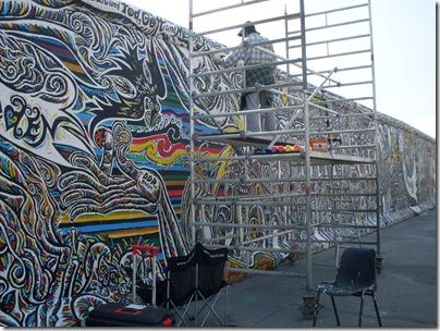 Un artista dipinge sulla east side gallery
