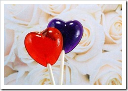 red and purple heart-shaped lollipops in front of roses