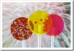 brown, yellow, and pink lollipops in foreground, fireworks in background