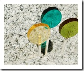 gold, teal, and avocado green lollipops on a granite bench