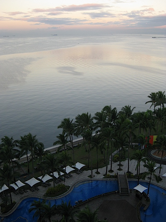 Sofitel Manila's swimming pool and gardens beside Manila Bay