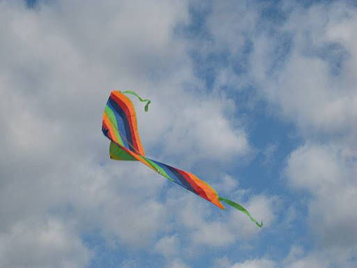 rainbow-colored kite in a blue sky
