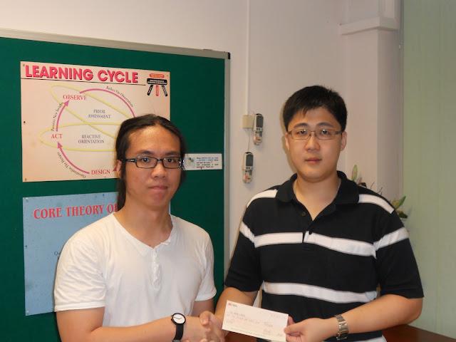 Ng Hong Kiang (left) receiving the Bursary Award from AJCAA President Lau Kiat Meng.