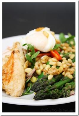 Sałatka z jajkiem w koszulce, kurczakiem i szparagami polanymi masłem czosnkowym z orzechami pinii
