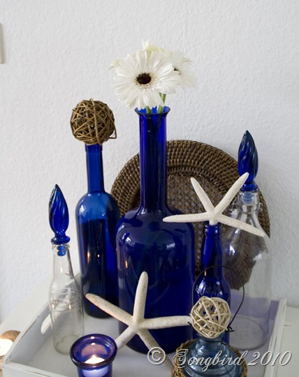 Decorative display for summer with blue glass and beach for Glass bottle display ideas