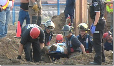 A rescue crew carries a man out on a stretcher after extricating him from a hole at a construction site.  (CBC)
