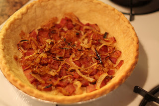picture of bacon and onion layered on bottom of pie crust