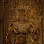 The devata's attractive face is distinctly Khmer, with a powerful, square shape. Her stomach is unmarked and her breasts are so full they press together, a motif that is hardly seen at Angkor Wat.