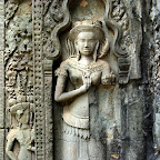 A Thommanon Devata (sacred female image) with pleated sampot and marked stomach holding her mudra over her heart. And there to the left we see yet another faceless devata holding three unidentified rods. Siem Reap, Cambodia http://www.Devata.org
