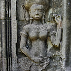 This Thommanon Devata (sacred female image) in Angkor Wat style has some unusual features. First is the long stemmed bud or garland in her left hand. King Suryavarman II holds a similar object in his portrait at Angkor Wat. Her left hand holds three tubular objects that are rare at Angkor Wat. Chalk? A Vajra? Chimes? There are a mystery. Her stomach, unlike most of her friends, is distinctly marked with lines. Finally, in addition to 6 seed pods coming out of the bottom of her crown, we see two dangling jewelry items, possibly representing her rank. Siem Reap, Cambodia http://www.Devata.org