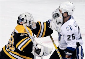 Tim Thomas gives Martin St. Louis a facewash with his glove