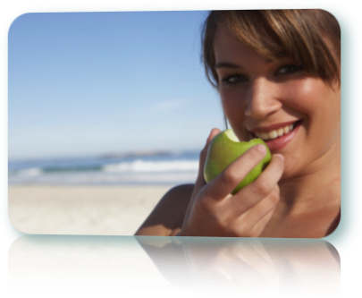 Woman biting into a green apple. Ocean background.