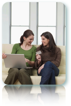 Two women sitting on the couch using a laptop and talking about applying for a credit card.
