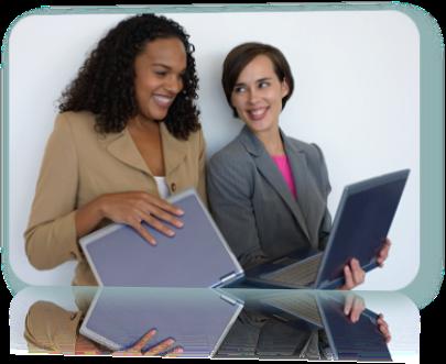 Two women, both holding laptops, smiling.