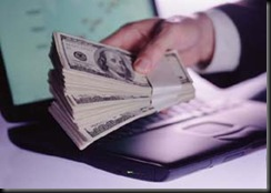 closeup of buinessman's hand holding wad of banknotes with laptop computer in background