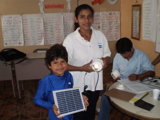 An AVODEC woman and her child recieve a solar lamp.