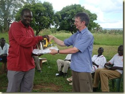 Pastor Richard receiving beekeeping equipment from Tim