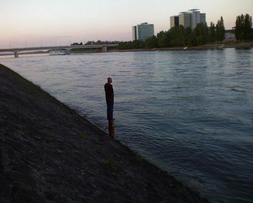 Budapest,  Duna,  oszlopszent, urban legends, Danube, Donau, A sziklára feljutni nem volt nehéz feladat. Sokan megtehették már esztendőkön át ezt az utat, mert lépcsőszerű kapaszkodók vezettek rajta felfelé. Fent, az oszlop talapzata körül virágok, gyümölcsök hevertek a kövön, bizonyságául a nép áhítatos tiszteletének az oszlopszent iránt.  András intett a kísérőinek, hogy maradjanak vissza, maga pedig az öreg szingaléz nyomában kapaszkodni kezdett, és hamarosan ott állt a szikla tetején, a gránitoszlop tövében. Az oszlop magasabb volt nála, felnyújtott karral elérhette volna a felső párkányát, ahol az oszlopszent csontos lába állt.  Az öreg szingaléz lerakta ajándékait, homlokával háromszor megérintette a földet, és gyorsan leereszkedett a szikláról. Bizonyára nem tartotta magát méltónak arra, hogy tartósan ott időzzék a hatalmas szent közvetlen közelében.  András azonban fönn maradt, és különös érzésekkel eltelve szemlélni kezdte a dermedten álló, különös alakot. Mintha bronzból öntötték volna, oly mozdulatlan nyugalom ülte meg az egész testet. A két csontos kar halottan lecsüngött, a szemekben nem volt élet, láttak ugyan, de nem néztek, csak a hosszú fehér szakáll rezdült meg néha-néha a szél könnyű fuvallatától. Az oszlop tetején valóban fecskék fészkeltek, egy fecske éppenséggel ott ült az oszlopszent vállán, és mintha titkokat sugdosna a fülébe, halkan csivitolt.  - Ramájun! - szólította meg András percek múltával az eleven szobrot. - Ramájun! Téged a világ nagy bölcsnek tart, és a híred hozzám is eljutott... A nép azt mondja, hogy te mindent tudsz, szent és mindenható vagy, és hogy nincsenek előtted titkai sem a sorsnak, sem a természetnek.  A szent mintha egy árva szót sem hallott volna András beszédéből.  - Ramájun! - kiáltott hangosabban András. - Ha mindentudó vagy, mondd meg, miért kerget engem a sors tengereken, világrészeken keresztül. Miért nem lelek én pihenést sehol a földön? Mondd meg nekem, Ramájun, és adj tanácsot, mit tegyek.  A szent nem moccan