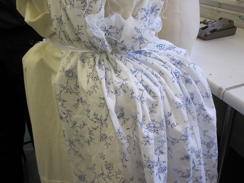 Draping overskirt fabric over bumpads and petticoat