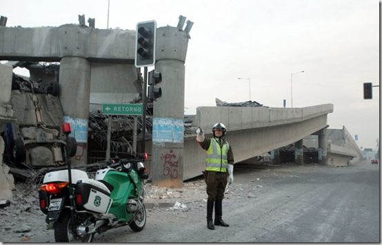 A police officer controls the traffic aside of an elevated highway that collapsed in Santiago following a powerful earthquake in central Chile, Saturday, Feb. 27, 2010.   (AP Photo/David Lillo)