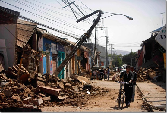 A resident walks along a damaged street in Talca, Chile, Saturday, Feb. 27, 2010, after a powerful earthquake struck central Chile. (AP Photo/Roberto Candia)