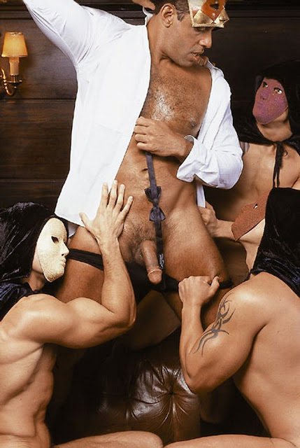 alexandre frota dressed only in an open shirt surrounded by his masked friends who adore him on their knees