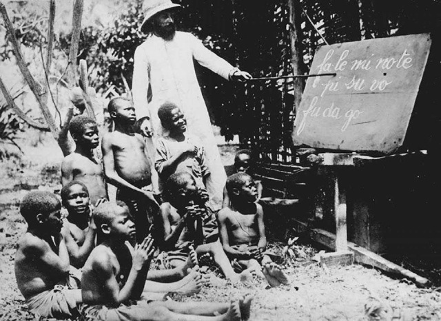 Reading Lesson in the Congo. A class of boys learns to read the local language in 1930 at the Jesuit school of Kwango in the Belgian Congo.