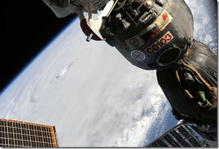 Olho do furacão Earl; à direita, nave russa Soyuz acoplada à ISS (Foto: Douglas Wheelock)