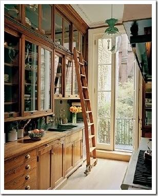 cocina con muebles de madera de techo a suelo y escalera