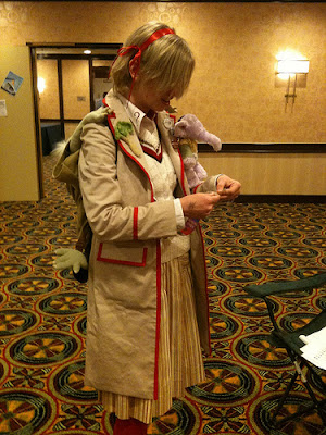 Young blonde woman in a Fifth Doctor variant costume.
