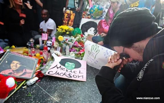 关于杰克逊 Jesse Buckingham, 24, of Los Angeles, sits at a sidewalk shrine of flowers, candles and notes adorning the star of Michael Jackson on the Hollywood Walk of Fame in Los Angeles Friday, June 26, 2009.Jackson died Thursday of an apparent heart attack.(AP Photo/ Reed Saxon)