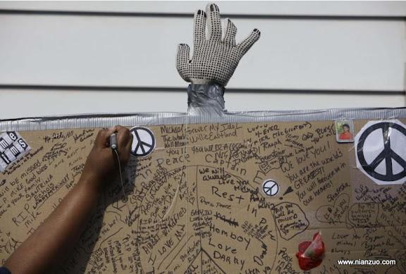 关于杰克逊 A mourner signs a condolence poster as people gather outside the boyhood home of pop star Michael Jackson Friday, June 26, 2009, in Gary, Ind. Jackson, 50, died Thursday of an apparent heart attack. (AP Photo/ M. Spencer Green)