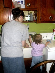 Elaine washing dishes with mommy