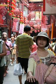 上頭的紅色竹編裝飾品和周圍的招牌掛布挺搭,倒是後邊這位遊客著了一襲小蜜蜂造型服殺了風景。