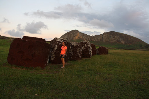 Amy with some pukao (moai hats), in the background Rano Raraku