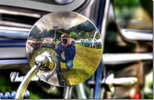 photographer&#39;s reflection in the back of a classic car mirror copy