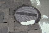 Note that  manhole ring is slightly lower than pavers and gap at ring is wide and random allowing sand to wash from gaps.
