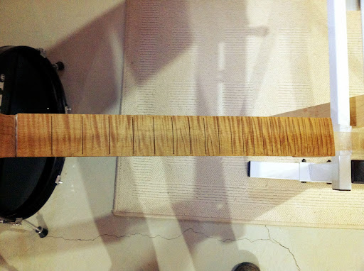This is what a roasted curly maple fretboard looks like with a thin coat of sealer on it. Zowie!