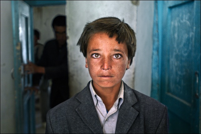 "His family is poor, his clothes used. But 15-year-old Ali Aqa isn't deterred: He plans to be a lawyer. Childhood memories include Taliban occupation of his village in Bamian. ""They burned everything, even my school,"" he says. ""I pray to God no regime comes like that again."" Bamian, Afghanistan. 2007.National Geographic, February 2008, Hazaras.final print_milan"