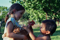 Mariah and Carlos (my sister and brother) play with one of our chickens. We always had hens mainly for their eggs, my parents still keep four or five even though they don't go through as many eggs with the kids out of the house.