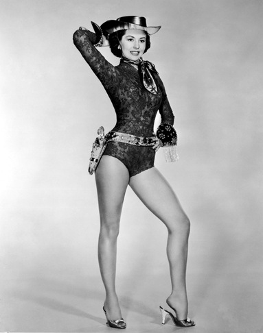 1956: American actor and dancer Cyd Charisse wearing a costume leotard with a cowgirl hat, sequined holsters, a scarf, and cuffs and standing with one hand on her hip and the other behind her head, in a promotional portrait for director Roy Rowland's film, 'Meet Me in Las Vegas.'