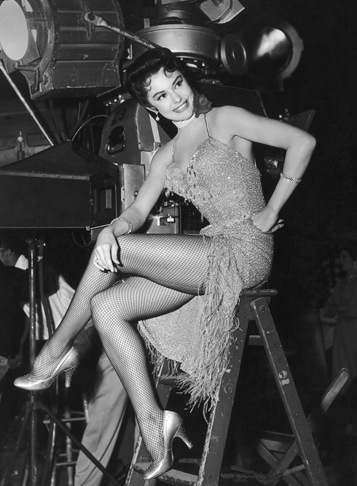 1956: Full-length image of American actor and dancer Cyd Charisse sitting on top of a ladder beside stage lights on the set of director Roy Rowland's film, 'Meet Me in Las Vegas'. She is wearing a sleeveless, beaded dress with feathered fringes and fishnet stockings.