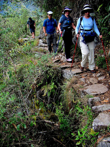 Hikers pass over a retaining wall supporting the Inca Trail